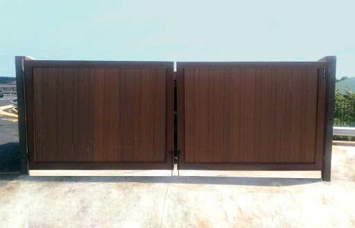 A brown wood grain Composite Dumpster Gate  has one latch down the center for easy and frequent access.