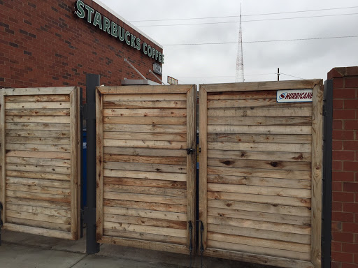A beautiful wood stained, brick and steel gate dumpster enclosure  outside of starbucks in Richmond Virginia