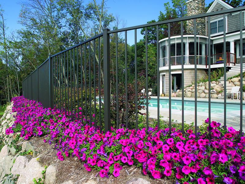 Black matte ornamental aluminum from Ultra Fence sits behind beautiful pruple flowers and a new stone patio.